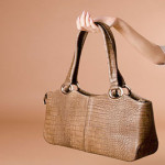 Hand holding leather handbag on the beige background